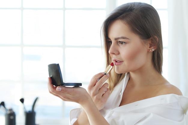 Jonge vrouw die rode lippenstift toepast.