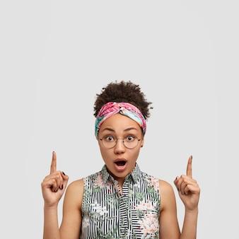 Jonge vrouw die ronde oogglazen en kleurrijke bandana draagt
