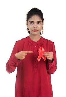 Jonge vrouw die rood lint hiv, aids-voorlichtingslint, gezondheidszorg en geneeskundeconcept tonen
