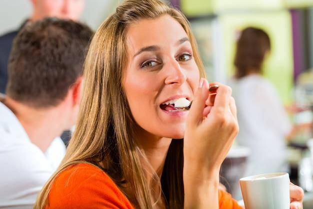 Jonge vrouw die room in koffie eet