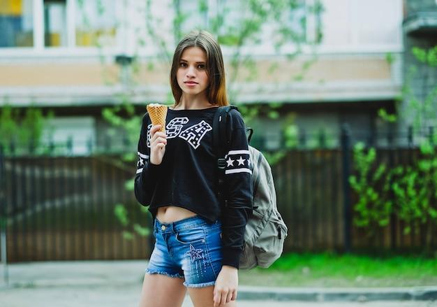Jonge vrouw die roomijs zonnige dag in openlucht eet