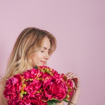 Jonge vrouw die roze boeket tegen roze achtergrond bekijkt