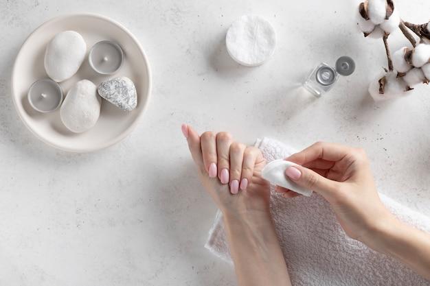 Jonge vrouw die roze nagellak met vlekkenmiddelvloeistof verwijdert. persoonlijke hygiëne en zorgconcept. witte betonnen muur, plat lag.