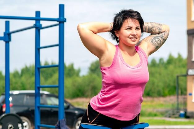 Jonge vrouw die rugverlengingsoefeningen uitvoert met behulp van een hyperextensiebank voor buitenoefeningen