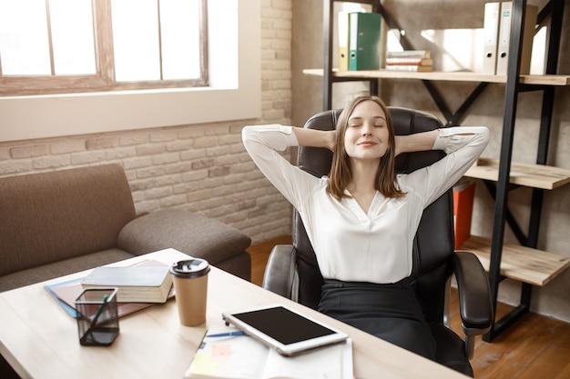 Jonge vrouw die rust heeft. ze zit aan tafel in de kamer met gesloten ogen. model glimlach. ze houdt handen achter haar hoofd.