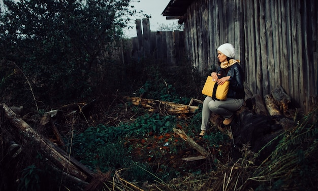 Jonge vrouw die 's avonds laat in de buurt van een oud houten huis zit