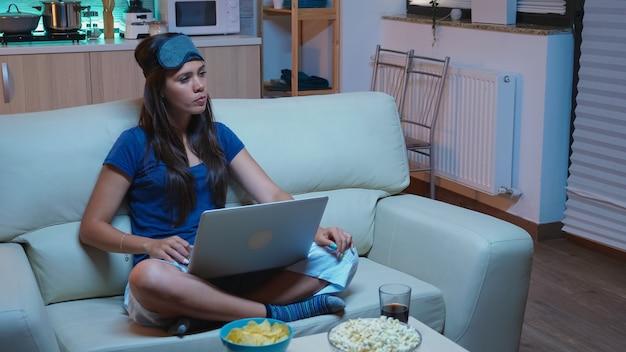 Jonge vrouw die 's avonds laat thuis werkt en op laptop schrijft terwijl ze tv kijkt. freelancer in pijamas lezen schrijven zoeken browsen op notebook met behulp van internettechnologie voor televisie