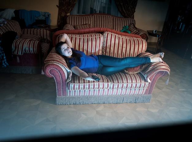 Jonge vrouw die 's nachts op de bank ligt en televisie kijkt