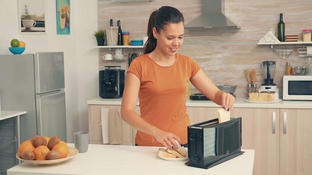 Jonge vrouw die 's ochtends een broodrooster gebruikt voor het ontbijt. huisvrouw die broodrooster gebruikt voor een heerlijk ontbijt. gezonde ochtend in gezellig interieur, heerlijke thuismaaltijdbereiding