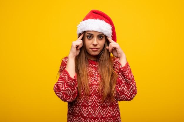 Jonge vrouw die santahoed draagt die een concentratiegebaar doet