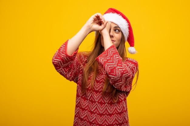 Jonge vrouw die santahoed draagt die het gebaar van een kijker maakt