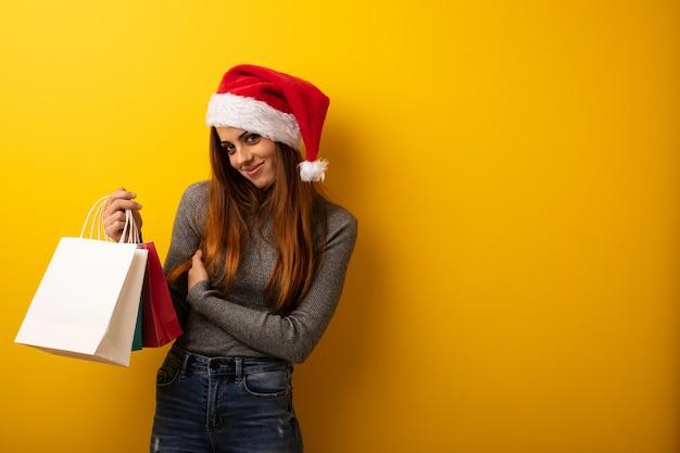 Jonge vrouw die santahoed het vieren kerstmisdag draagt