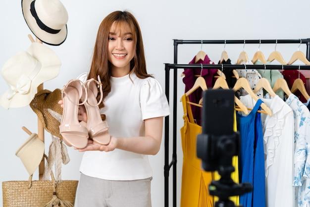 Jonge vrouw die schoenen en kleding online verkoopt door smartphone livestreaming, zakelijke online e-commerce thuis