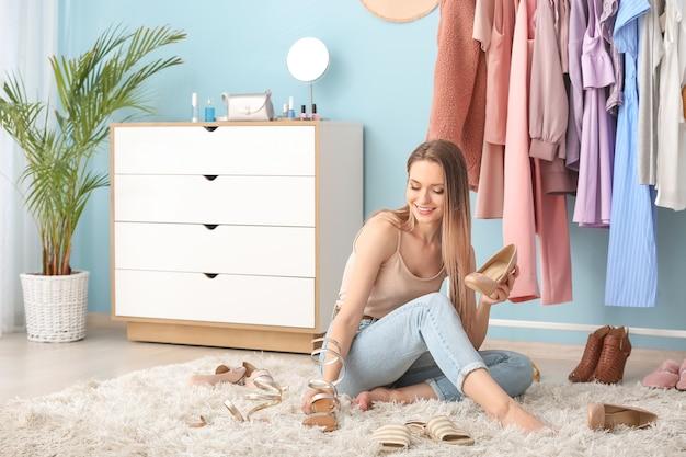 Jonge vrouw die schoenen in kleedkamer kiest