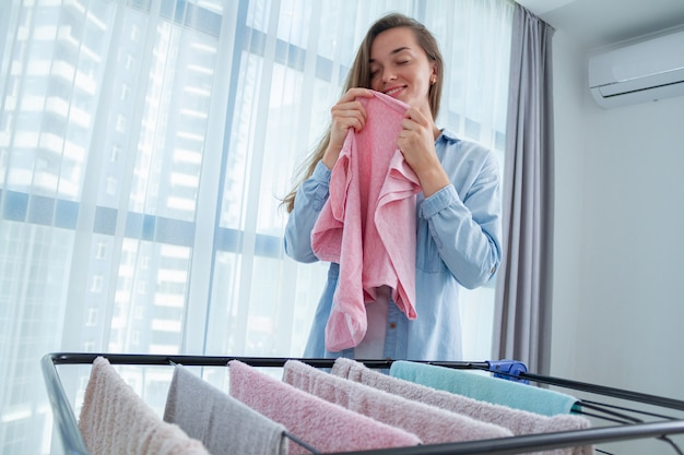 Jonge vrouw die schone kleren na wasserij thuis ruikt. wasdroger gebruiken na het wassen. huishoudelijke taken en huishouden