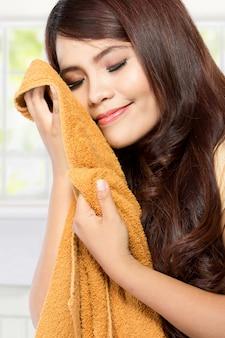 Jonge vrouw die schone verse wasserij ruikt