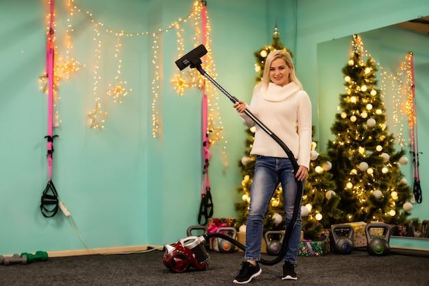 Jonge vrouw die schoonmaakt met stofzuiger, stofzuigt onder kerstboomnaalden met nieuwjaarsversieringen