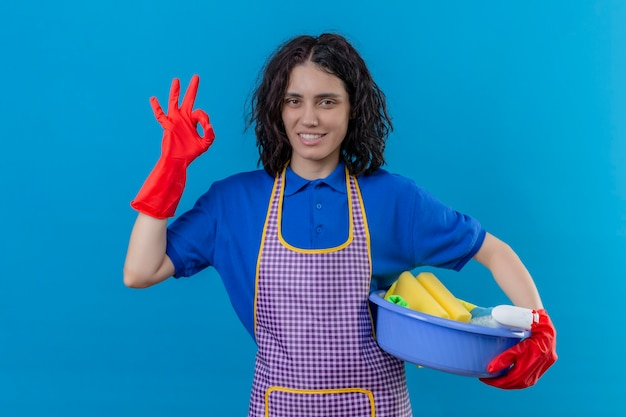 Jonge vrouw die schort en rubberhandschoenen draagt die bekken met het schoonmaken van hulpmiddelen houden die vriendschappelijk glimlachen doen ok teken die zich over blauwe achtergrond bevinden