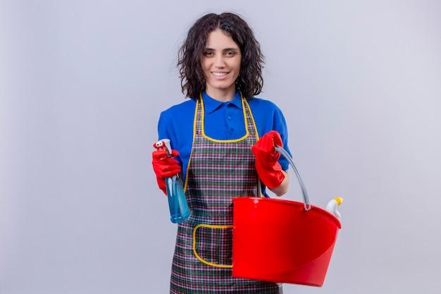 Jonge vrouw die schort en rubberhandschoenen draagt die emmer met het schoonmaken van hulpmiddelen en het schoonmaken nevel houden die camera positief en gelukkig status over witte achtergrond bekijken