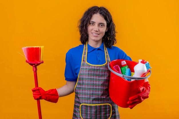 Jonge vrouw die schort en rubberhandschoenen draagt die emmer met het schoonmaken van hulpmiddelen en mop houden die vriendschappelijke status glimlachen over oranje achtergrond