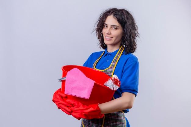 Jonge vrouw die schort en rubberhandschoenen draagt die emmer met het schoonmaken van hulpmiddelen houden die camera met glimlach op gezicht bekijken klaar om schoon te maken status over witte achtergrond