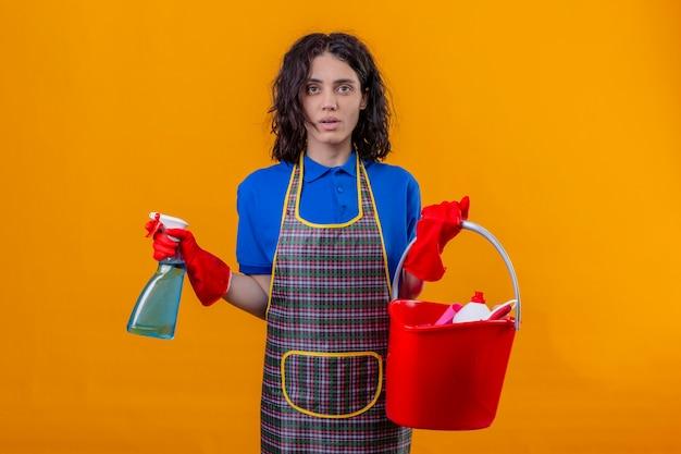 Jonge vrouw die schort en rubberhandschoenen draagt die emmer met het schoonmaken van hulpmiddelen houden en het schoonmaken nevel die verward status over oranje achtergrond kijken