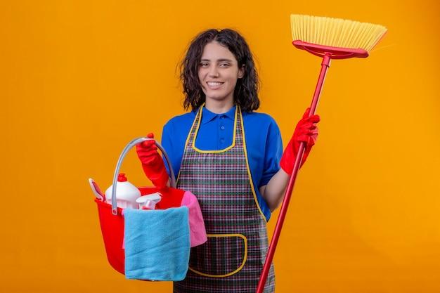 Jonge vrouw die schort en rubberhandschoenen draagt die emmer met schoonmakende hulpmiddelen en zwabber houden die vrolijk positief en gelukkig status over oranje achtergrond glimlachen