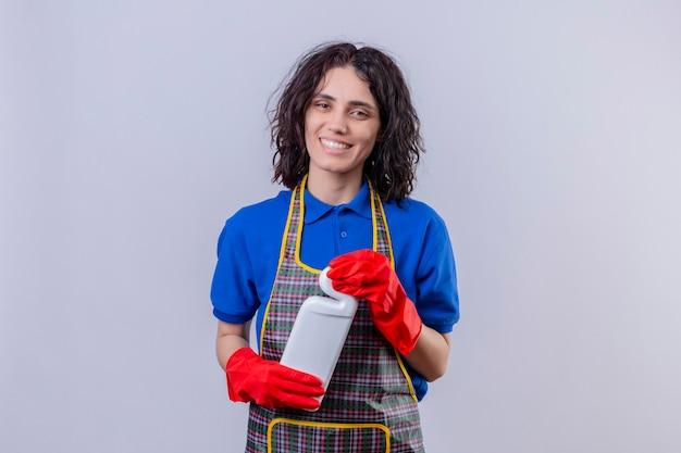 Jonge vrouw die schort en rubberhandschoenen draagt die fles met het schoonmaken van leveringen houdt die vrolijk glimlachen bekijkt camera die zich over witte achtergrond bevindt