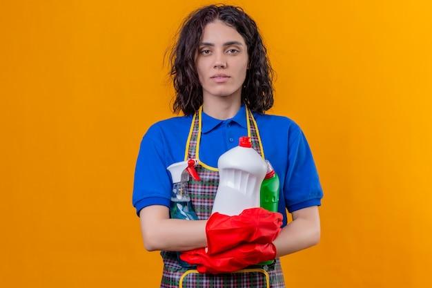 Jonge vrouw die schort en rubberhandschoenen draagt die schoonmaakproducten houdt die camera met ernstige zelfverzekerde uitdrukking bekijkt die zich over geïsoleerde oranje achtergrond bevindt