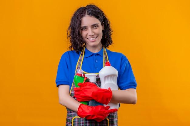 Jonge vrouw die schort en rubberhandschoenen draagt die schoonmakende levering houden die camera positief en gelukkig glimlachend status over oranje achtergrond bekijkt