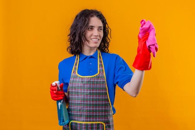 Jonge vrouw die schort en rubberhandschoenen draagt die schoonmakende nevel en deken houden die met gelukkig gezicht glimlachen klaar yo schoon status over geïsoleerde oranje achtergrond