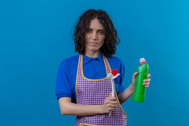 Jonge vrouw die schort en rubberhandschoenen draagt die schrobborstel en fles schoonmakende levering houden die zich zelfverzekerd bevinden over geïsoleerde blauwe achtergrond kijken
