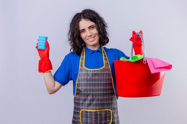 Jonge vrouw die schort en rubberhandschoenen draagt die spons en emmer met schoonmakende hulpmiddelen houden die camera met glimlach op gezicht bekijken die zich over witte achtergrond bevinden