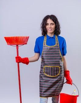 Jonge vrouw die schort en rubberhandschoenen draagt die zwabber en emmer met schoonmakende hulpmiddelen houden die camera met glimlach op gezicht bekijken die zich over geïsoleerde witte achtergrond bevinden