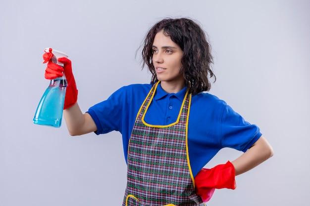 Jonge vrouw die schort en rubberhandschoenen met schoonmakende nevel dragen, klaar over geïsoleerde witte muur schoon te maken