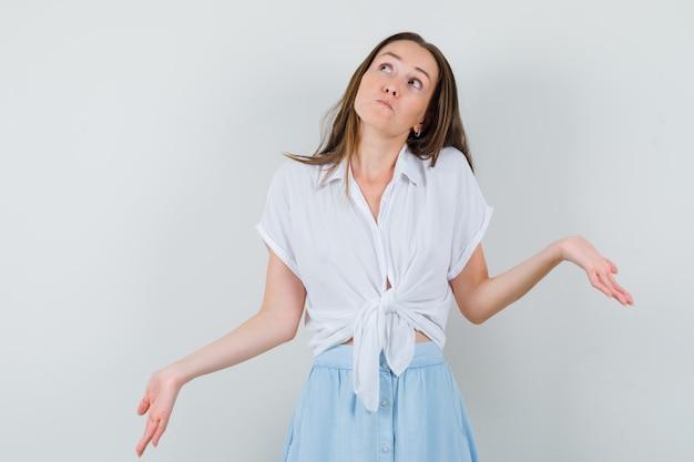 Jonge vrouw die schouders ophaalt in witte blouse en lichtblauwe rok en peinzend kijkt