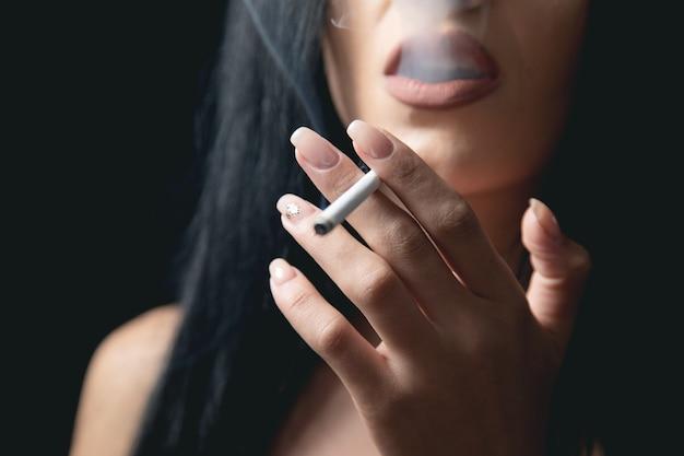 Jonge vrouw die seksueel een sigaret rookt