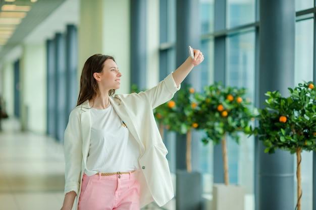 Jonge vrouw die seldie door smartphone in internationale luchthaven neemt die op vlucht wacht