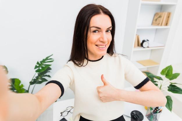 Jonge vrouw die selfie en duim omhoog toont neemt