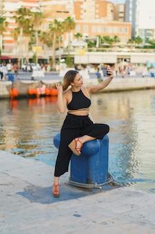 Jonge vrouw die selfie foto op smartphone.