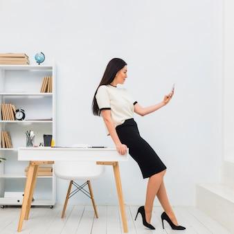 Jonge vrouw die selfie in bureau neemt