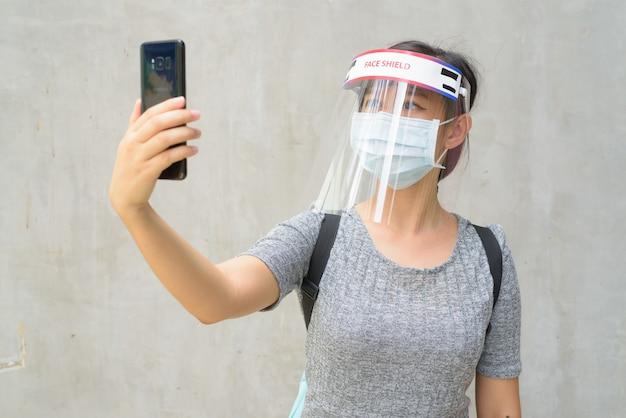 Jonge vrouw die selfie met masker en gezichtsscherm neemt voor bescherming tegen uitbraak van het coronavirus buitenshuis