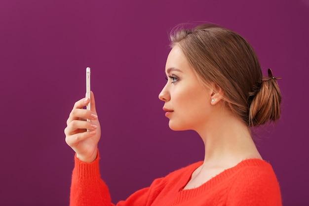 Jonge vrouw die selfie met mobiele telefoon op kleurenoppervlak neemt