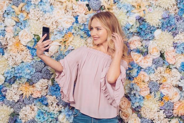 Jonge vrouw die selfie met smartphone nemen