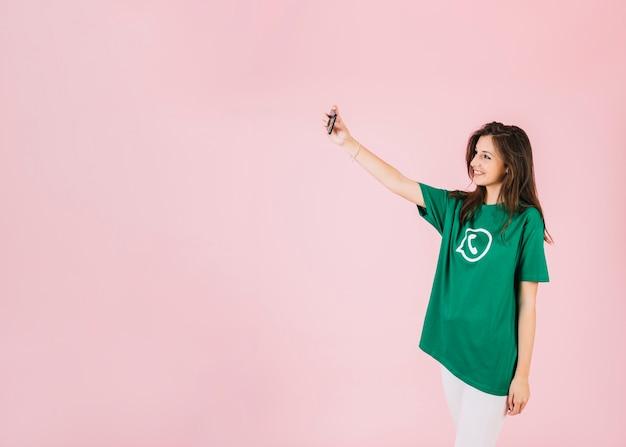Jonge vrouw die selfie met smartphone op roze achtergrond nemen