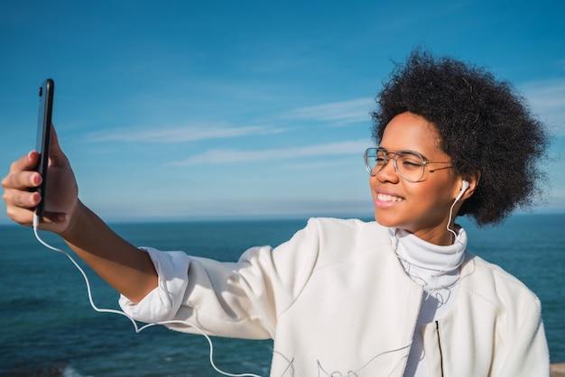 Jonge vrouw die selfies met telefoon neemt.