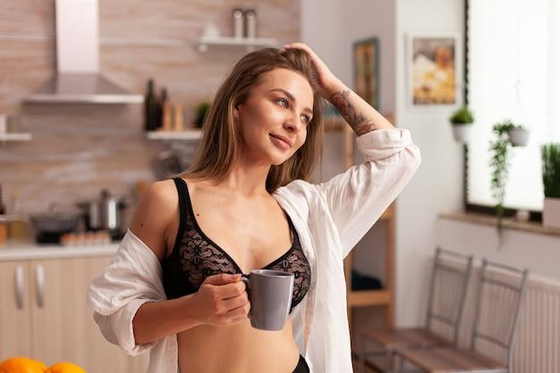 Jonge vrouw die sexy lingerie draagt tijdens het ontbijt in de thuiskeuken