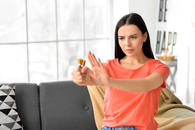 Jonge vrouw die sigaretten thuis verwerpt. concept van het weigeren van slechte gewoonte