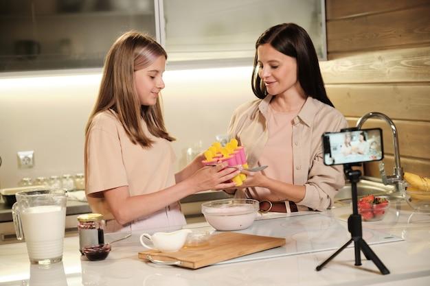 Jonge vrouw die siliconenformulieren voor zelfgemaakt ijs doorgeeft aan haar schattige tienerdochter over een glazen kom met gemengde ingrediënten