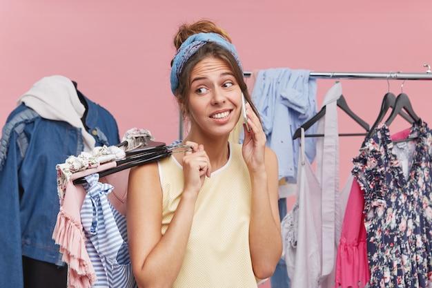 Jonge vrouw die sjaal op hoofd en vrijetijdskleding draagt, besluit haar garderobe op te frissen die winkelend in klerenwinkel doet en telefonisch spreekt